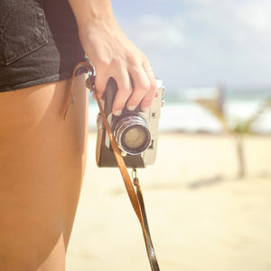Womans-Hand-Holdig-Vintage-Camera-On-Sunny-Beach